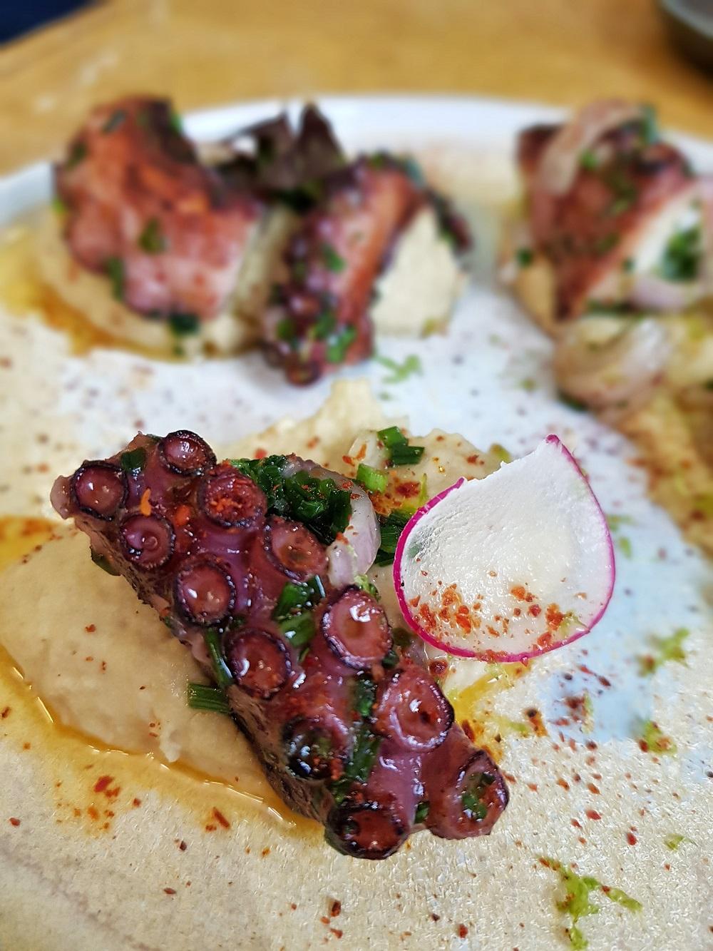 Tentacule de poulpe grillé, houmous maison, cébette et piment d'Espelette.
